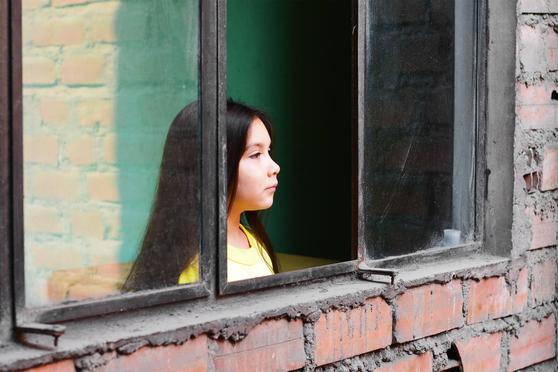 Young Brazilian girl gazing out of window