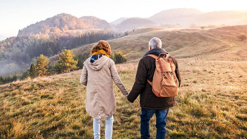 senior couple waling hand in hand through a field