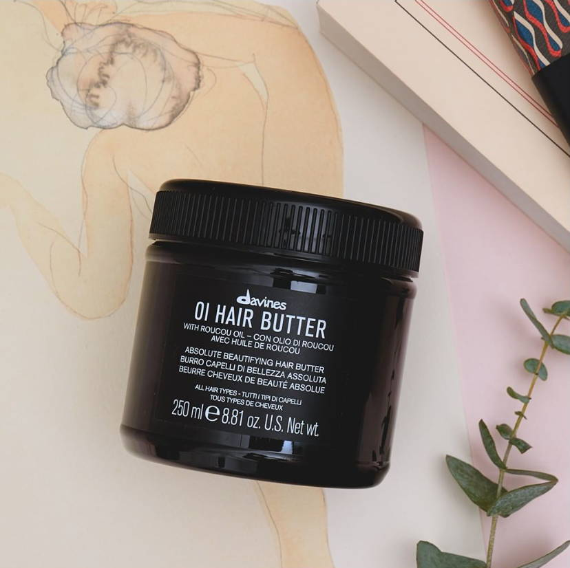Davines OI Hair Butter hair product on a multicolored background