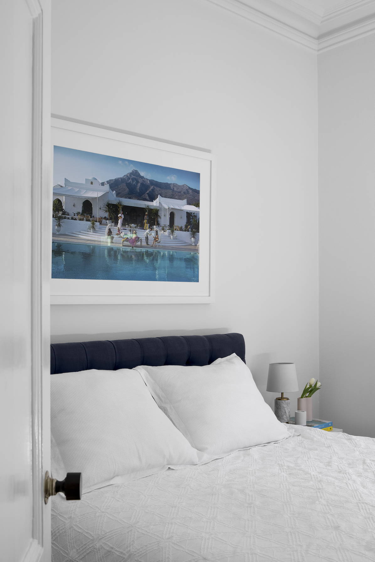 A poolside photograph by Slim Aarons, framed in white in a pretty bedroom setting