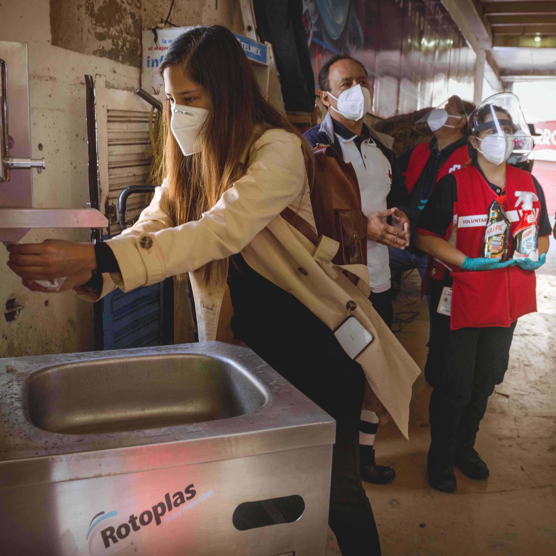 Mujer usando nuestra estación de agua en la Central de Abasto