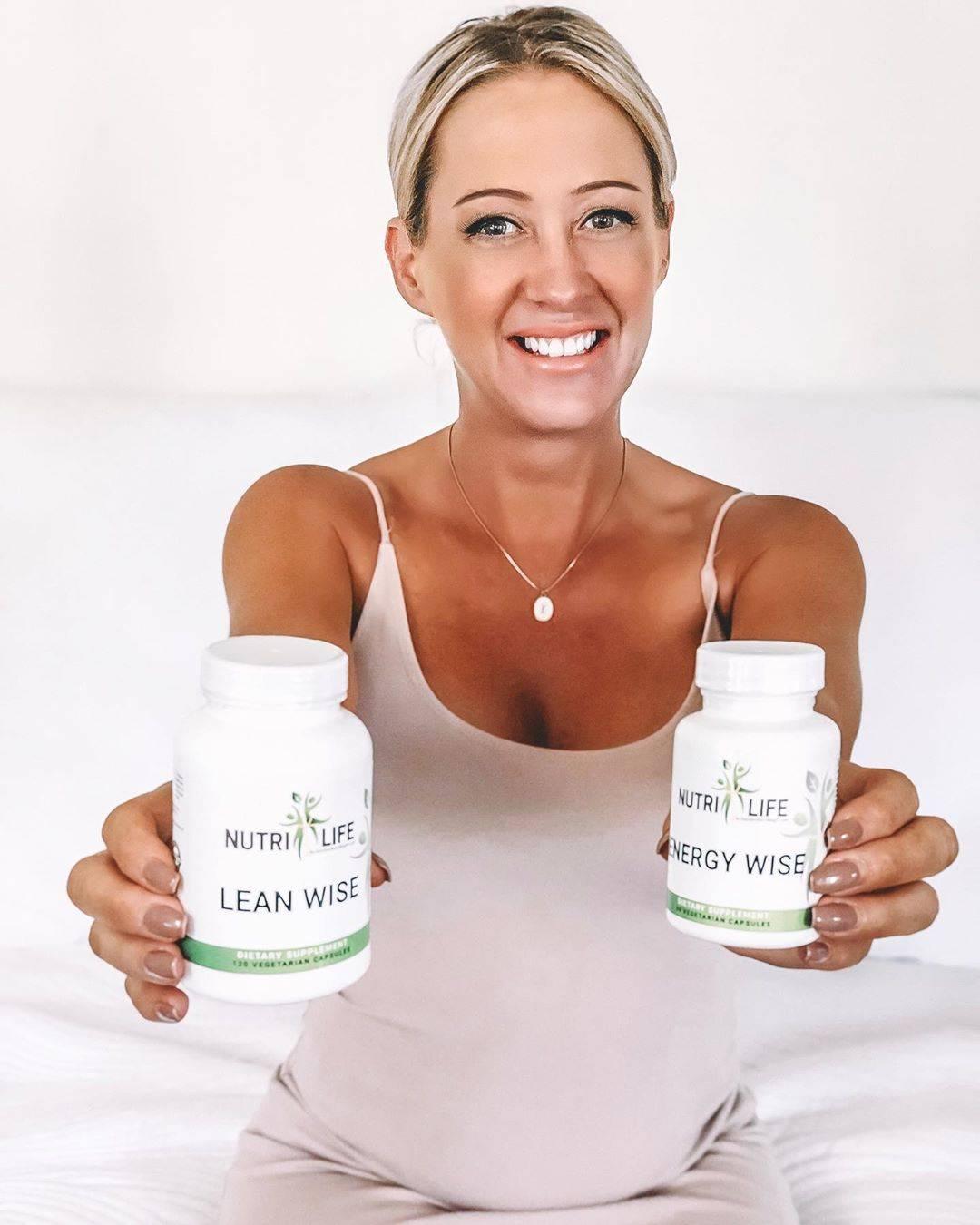 Woman holding a bottle of NutriLife LeanWise Dietary Supplement, and a bottle of NutriLife EnergyWIse Dietary Supplement