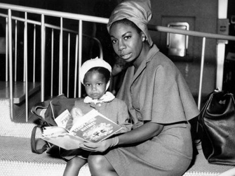 Nina simone with her daughter, sitting together and reading a book. Both are wearing dresses.
