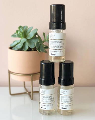 3 bottles of Davines Liquid Spell hair product in front of a plant