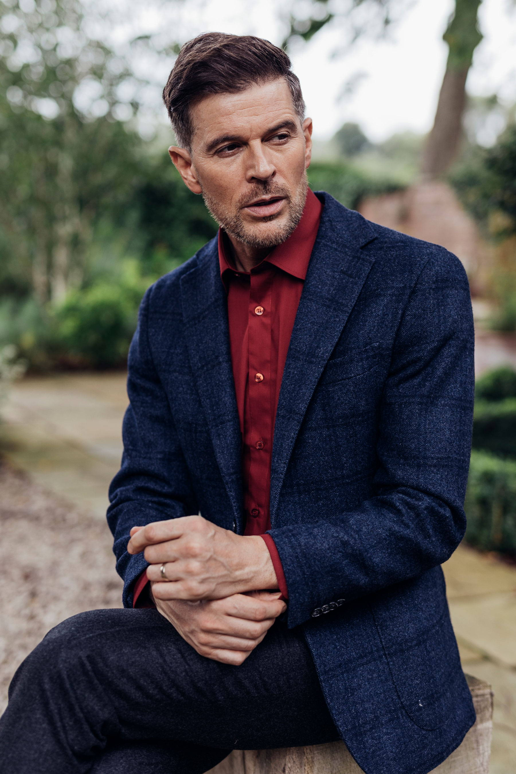 Man in burgundy shirt and navy suit