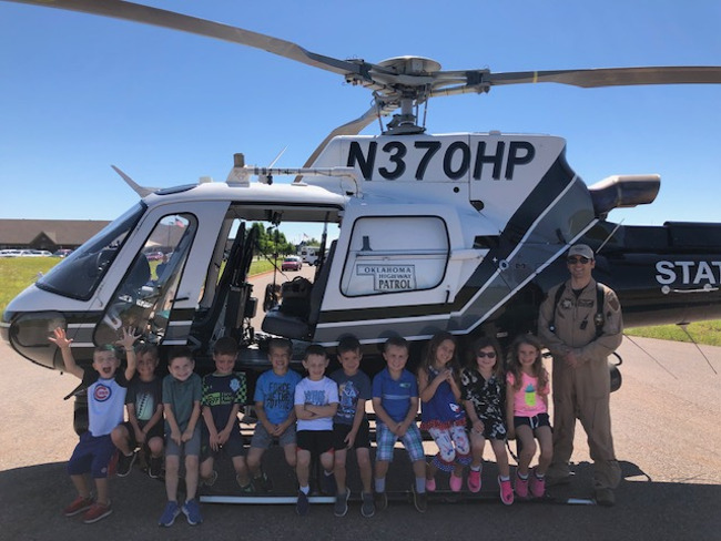 students on helicopter with state trooper