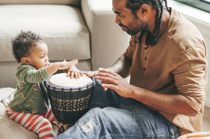 father and daughter playing drums