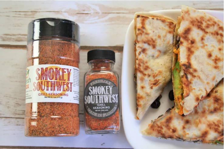 Two bottles of FreshJax Organic Smokey Southwest Grill Seasoning next to a plate filled with smokey southwest qesadillas.