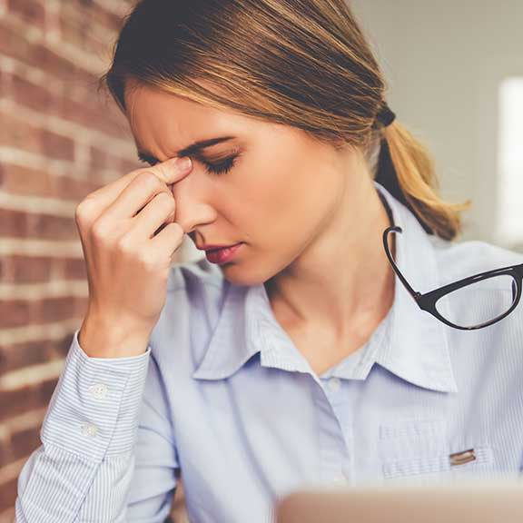 woman pinching her nose looking stressed