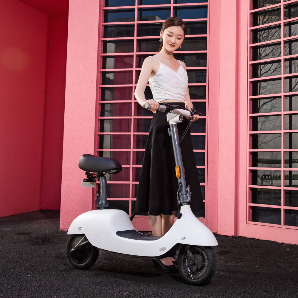 okai ea10 escooter white woman walking with scooter