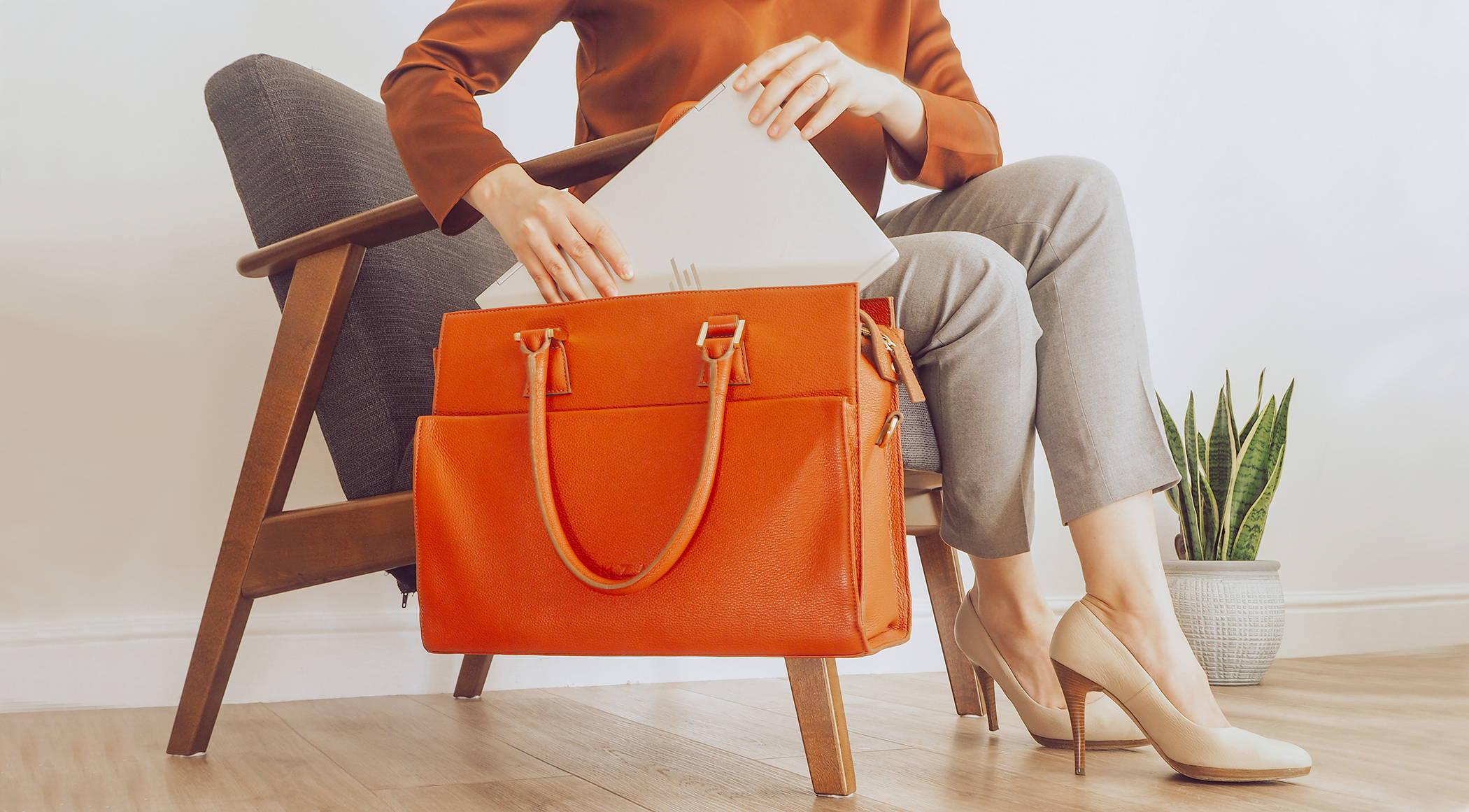 Close-up of business women in high heels placing laptop in leather laptop bag
