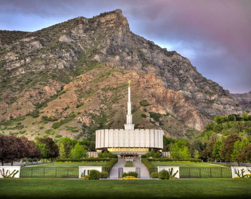 Provo Utah Temple standing in front of tall Utah mountains.