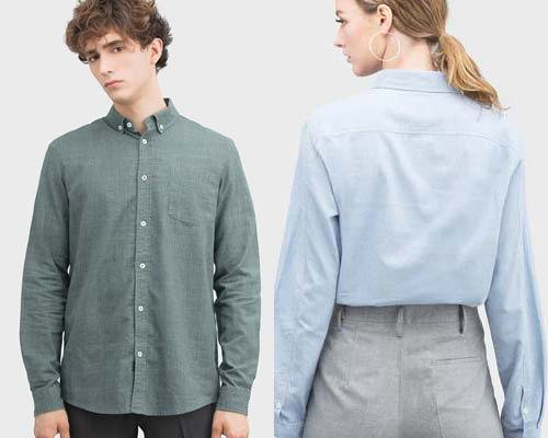 Man wearing olive green Cosmos Studio sustainable button down collar shirt and woman wearing light blue button down shirt tucked in to grey trousers