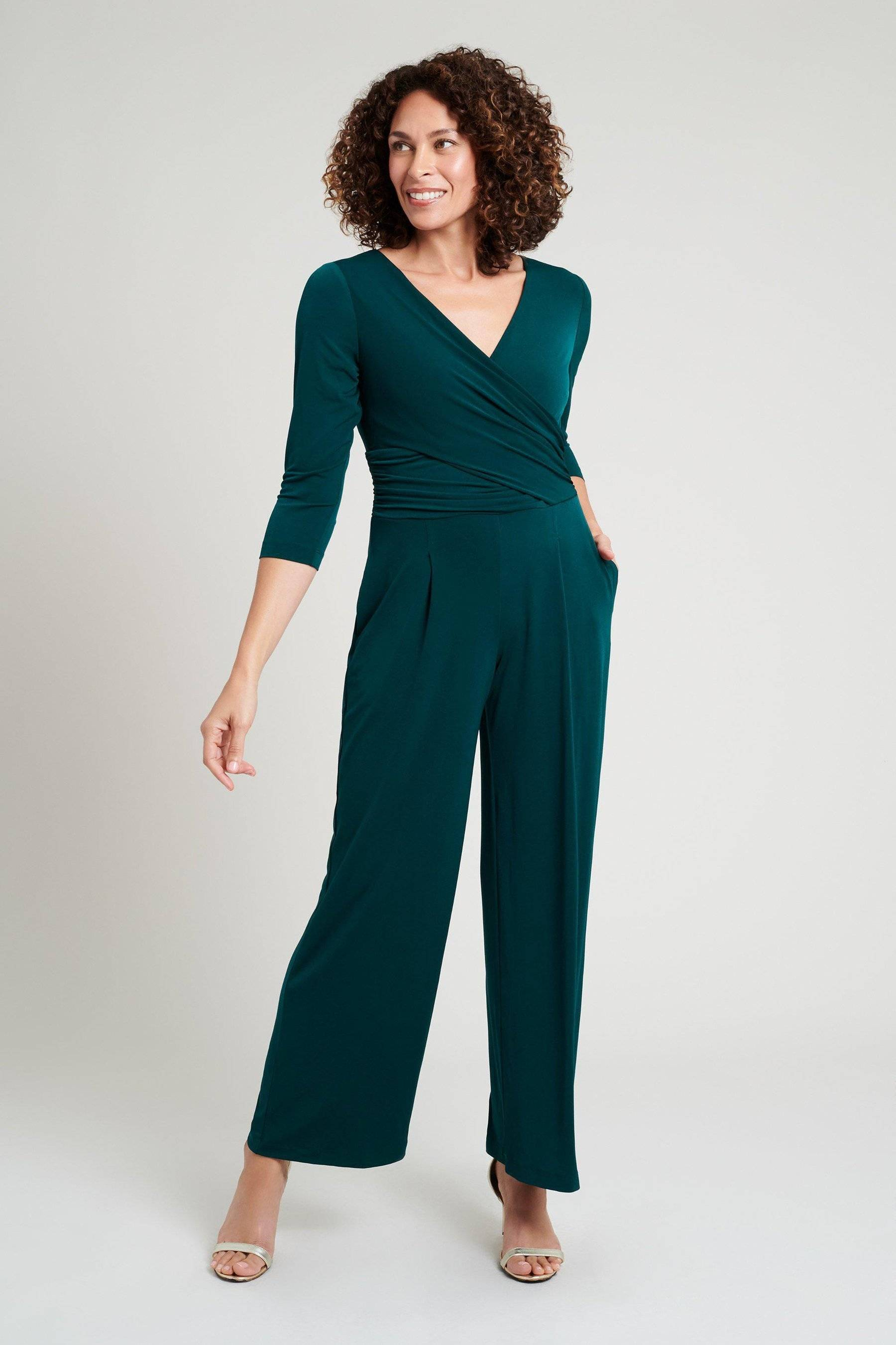 woman posing in emerald green three-quarter sleeve connected apparel jumpsuit