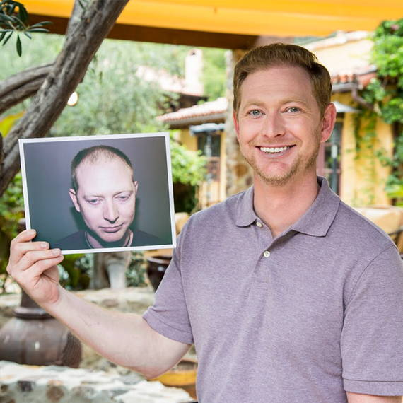 Blair holding a photo of himself with less hair