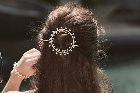 Close up view of the VINI hair wreath with white freshwater pearls, worn in a half up-half down hair-do.