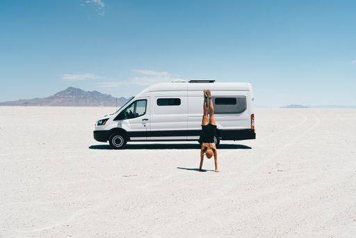 A woman does a handstand in front of a Mercedes 144 Sprinter van with Flarespace flares