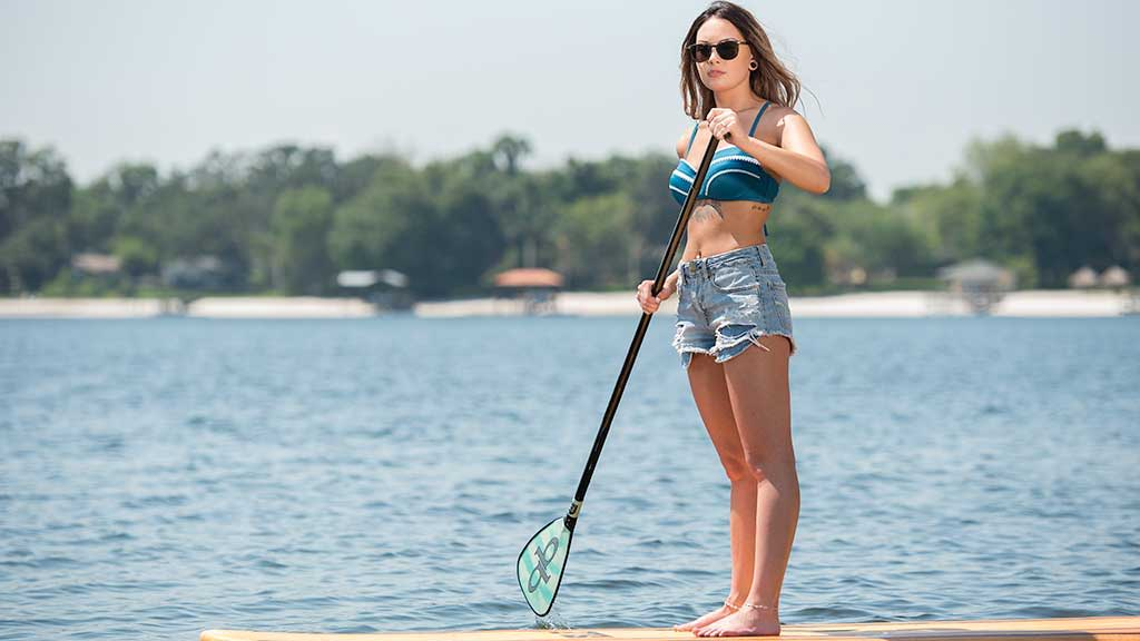 employee and client, Isabelle, paddle boarding