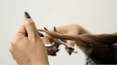 A woman cutting split ends from her hair