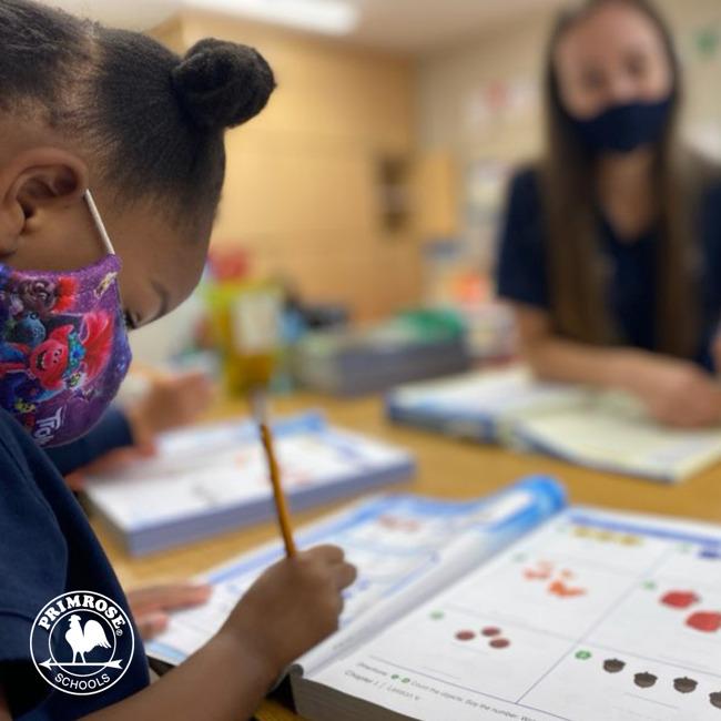 Masked Kindergartener Doing Math