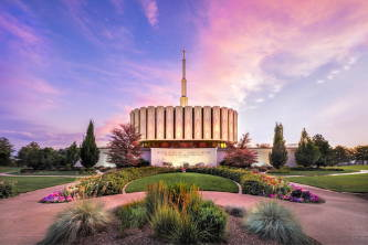 Provo Utah Temple and flowering grounds against a pink and blue sky.
