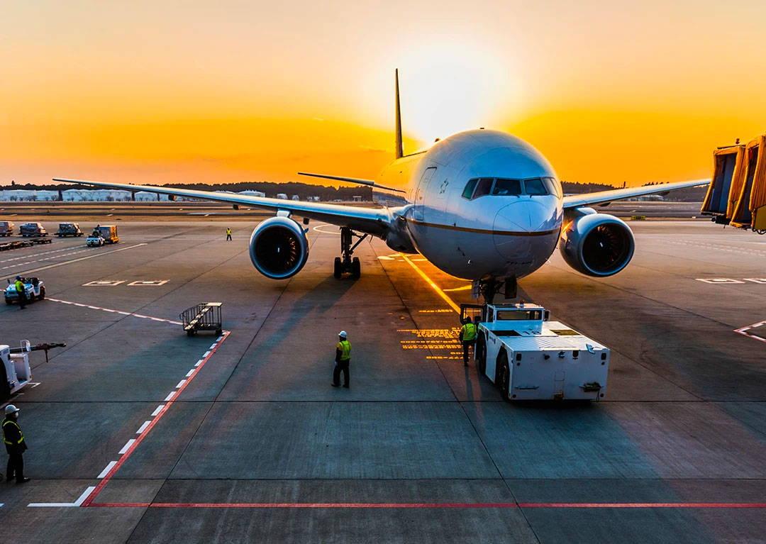 sunset behind airplane on tarmac