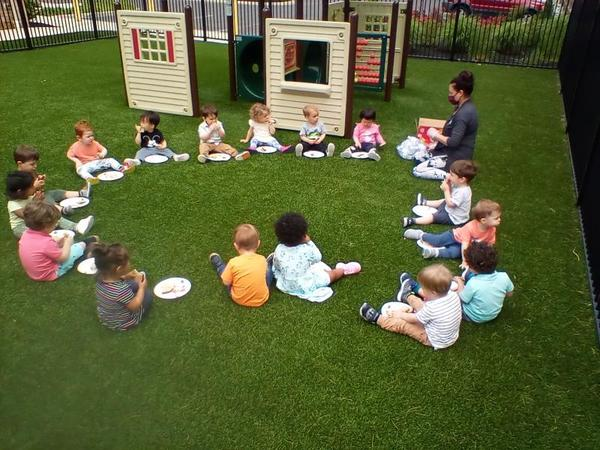Toddlers having a brown bag lunch outside