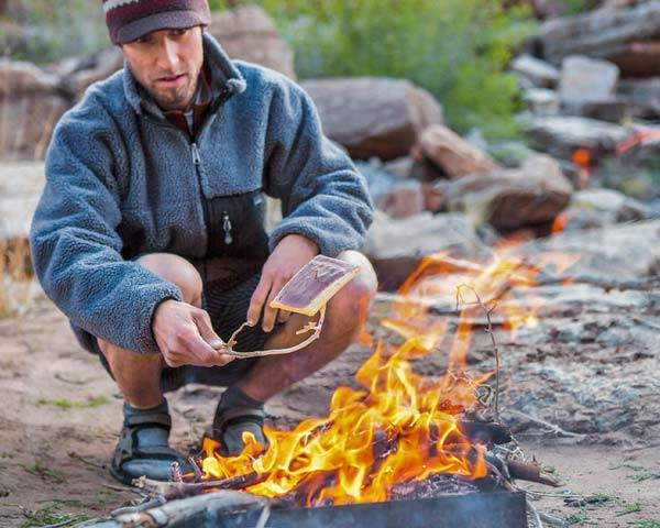 Man toasting food on the fire wearing blue Patagonia fleece and sandals
