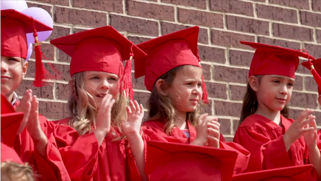 PreK graduates clap to their graduation song during their ceremony