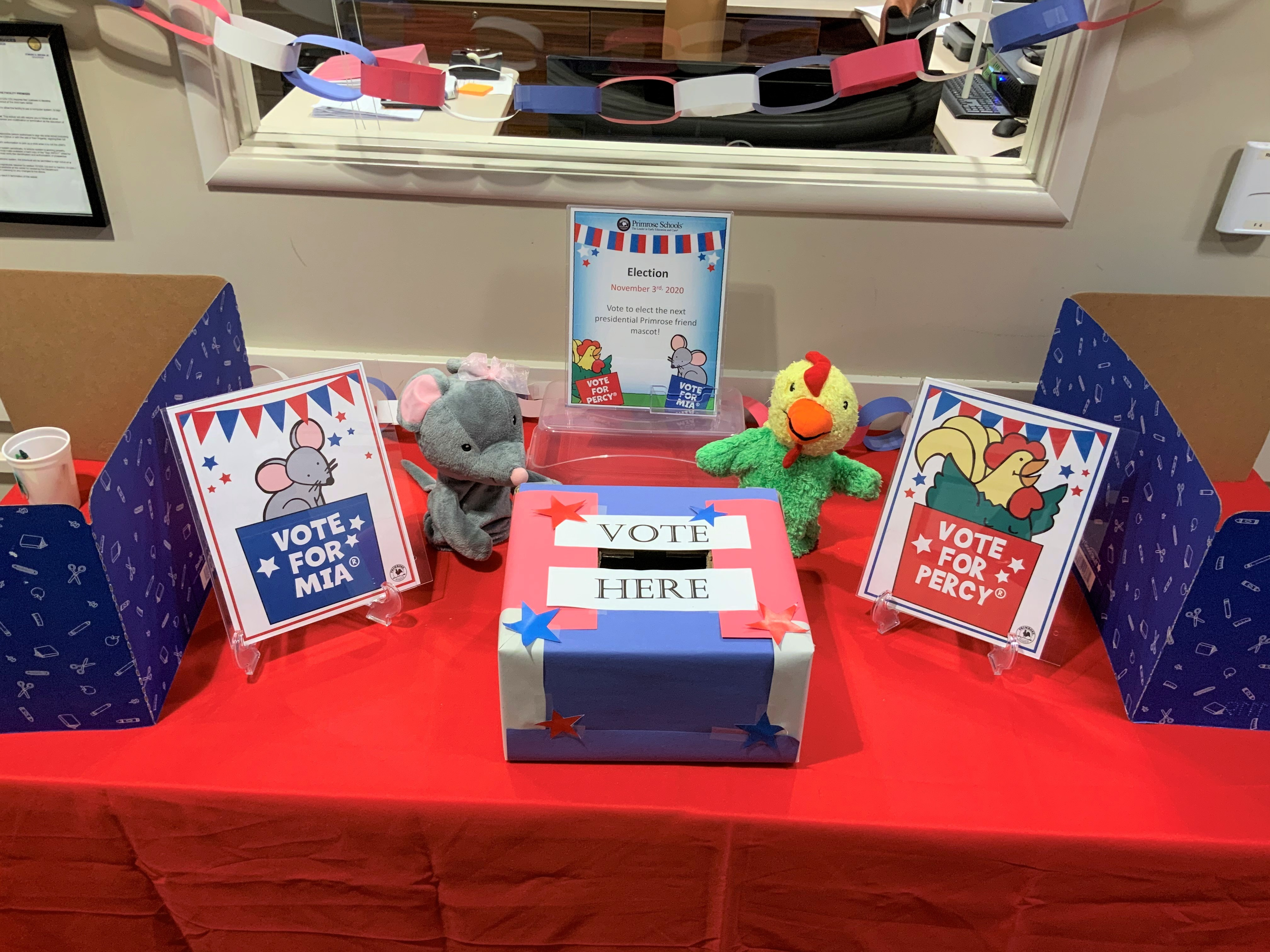 Voting booths with decorations and Percy the rooster and Mia the mouse puppets