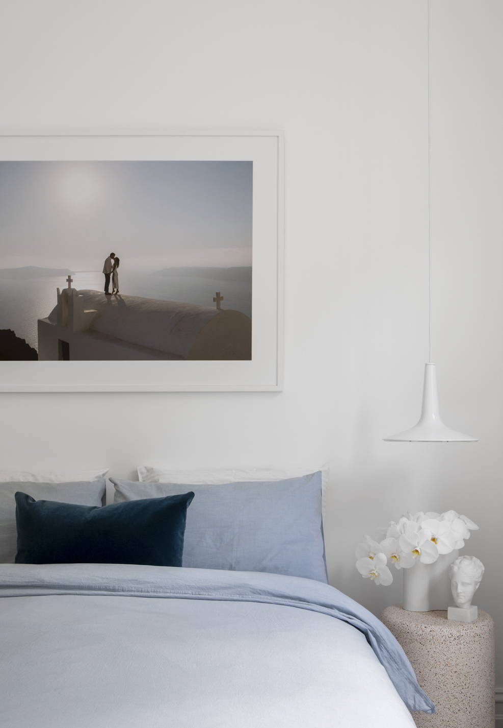 Wedding photography framed and hanging above a bed