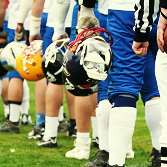 lineup of men holding helmets in football uniforms