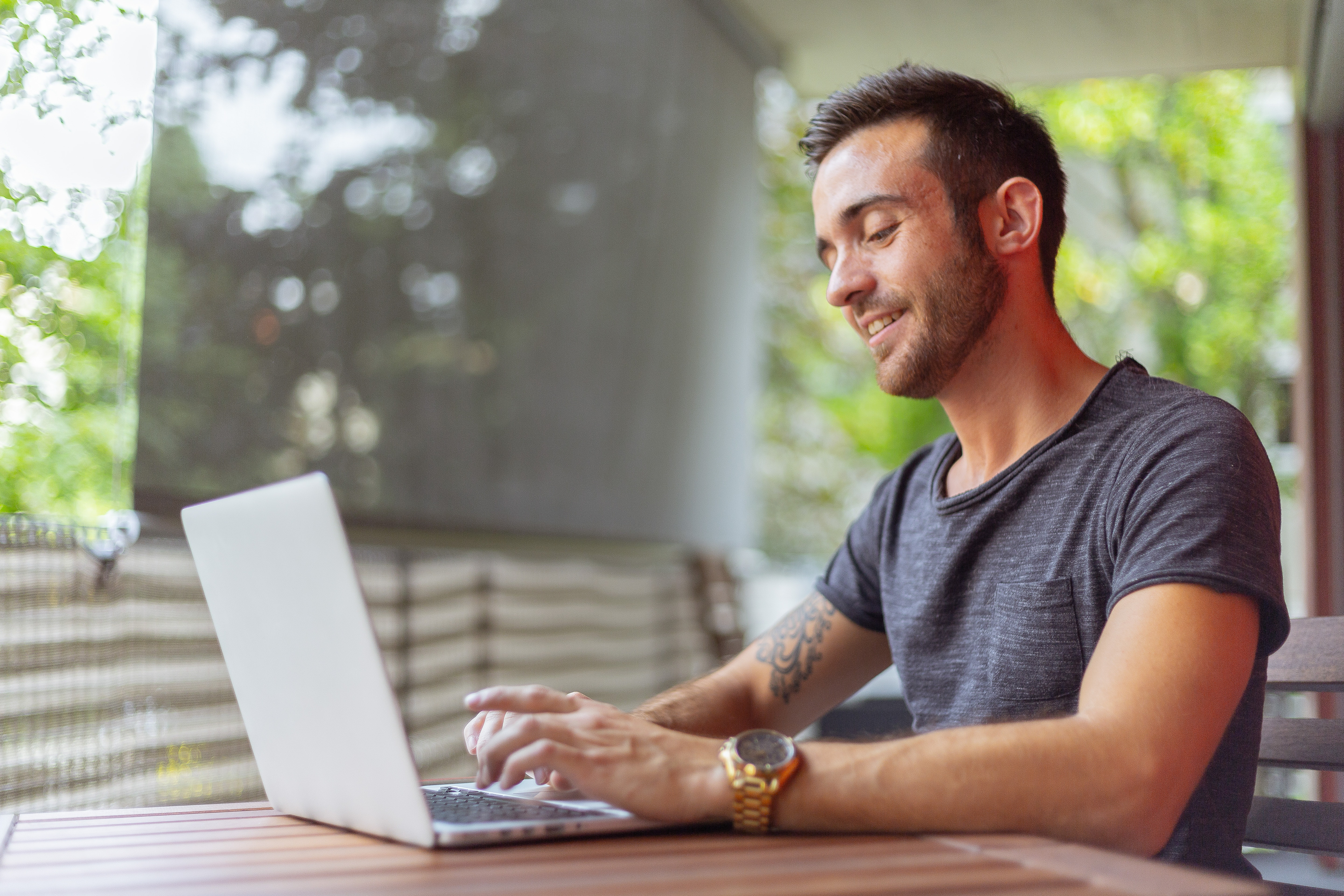 Image of an young white man with a beard tattoo, sitting in an open area typing on his laptop and smiling.