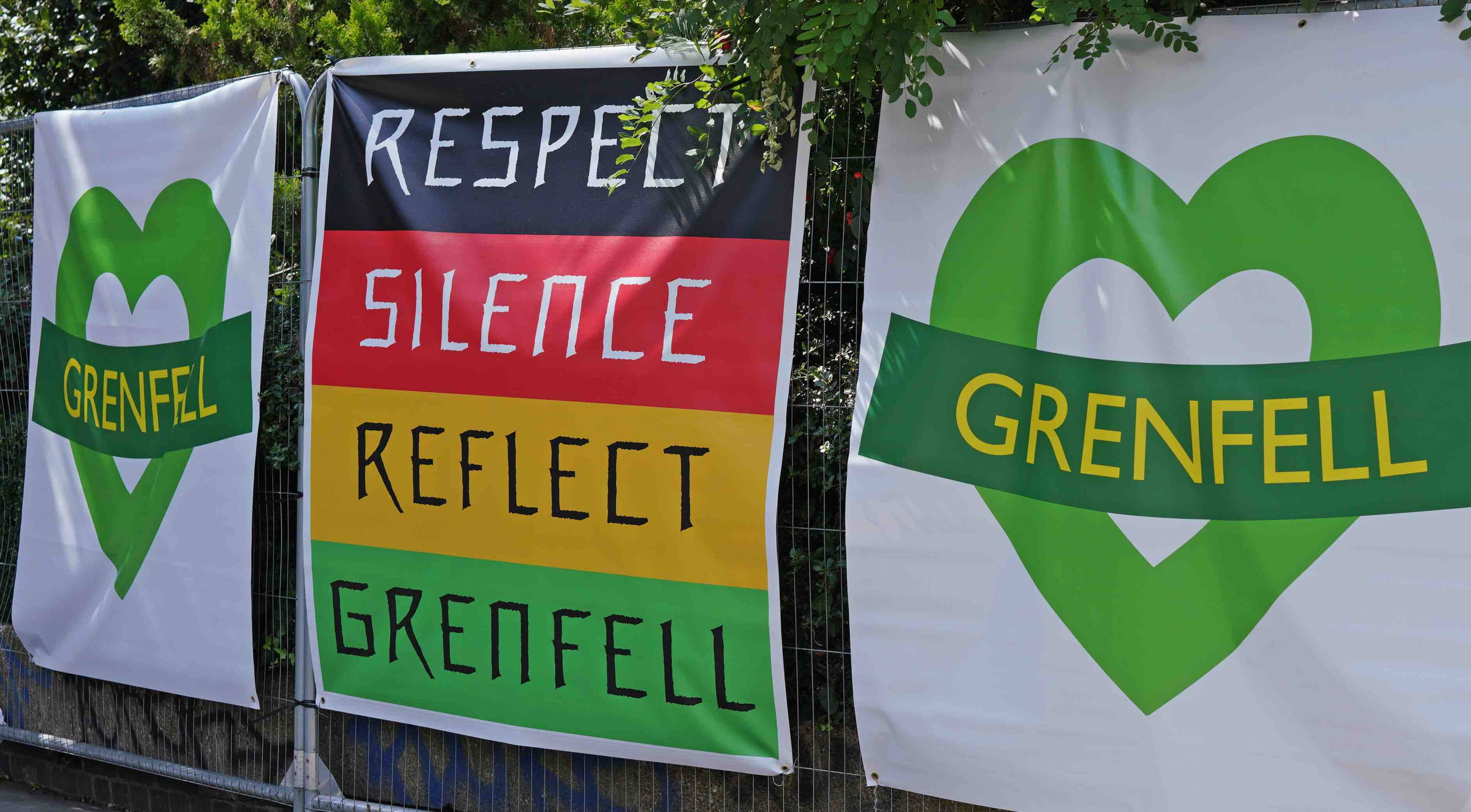 Grenfell green hearts and sign reading: respect, silence, reflect, Grenfell