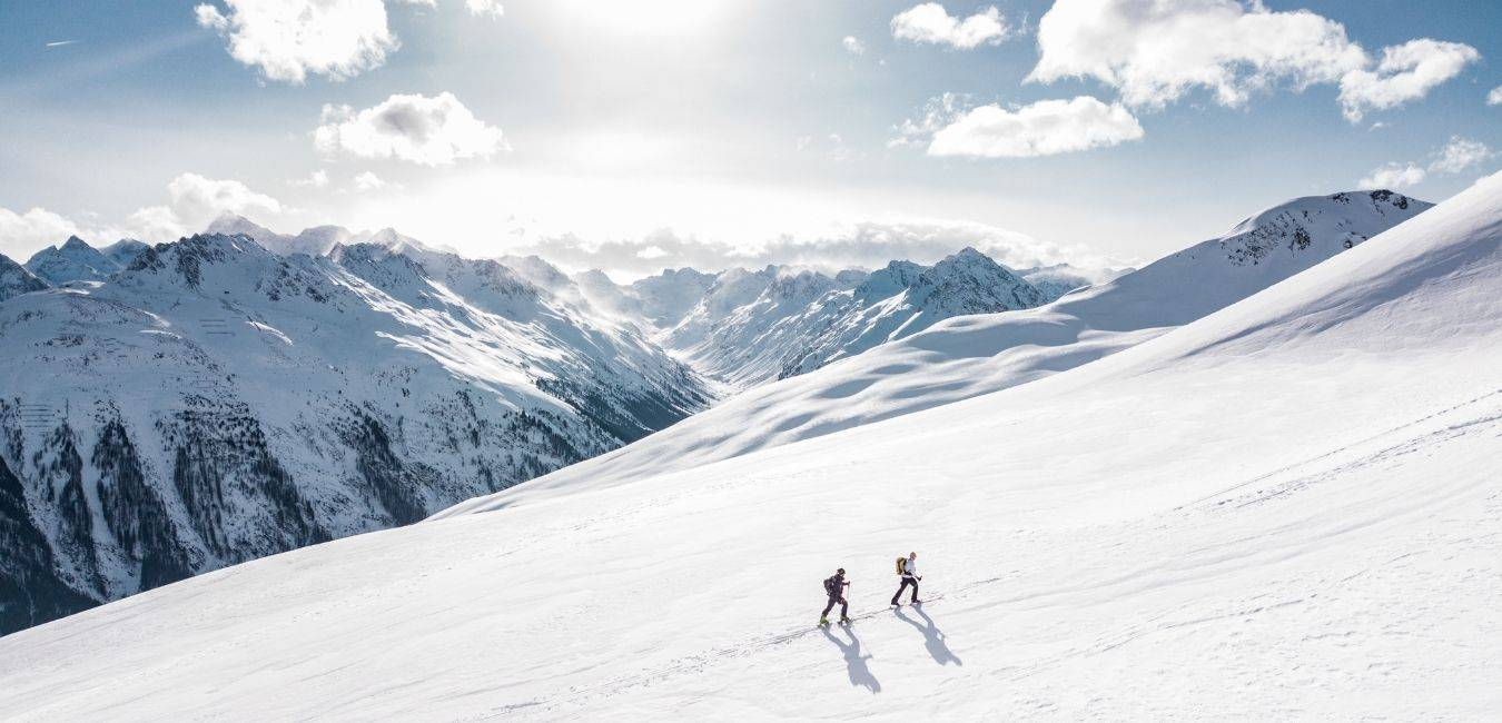 Sur la photo on voit deux freerider en train de faire du ski de randonnée faire l'ascension de la pente dans la poudreuse.