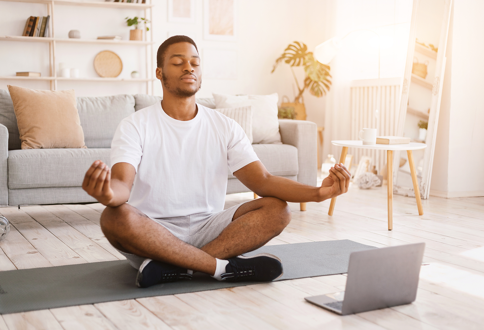 Photo of a black man meditating on the floor with a computer nearby, he is calm and smiling.