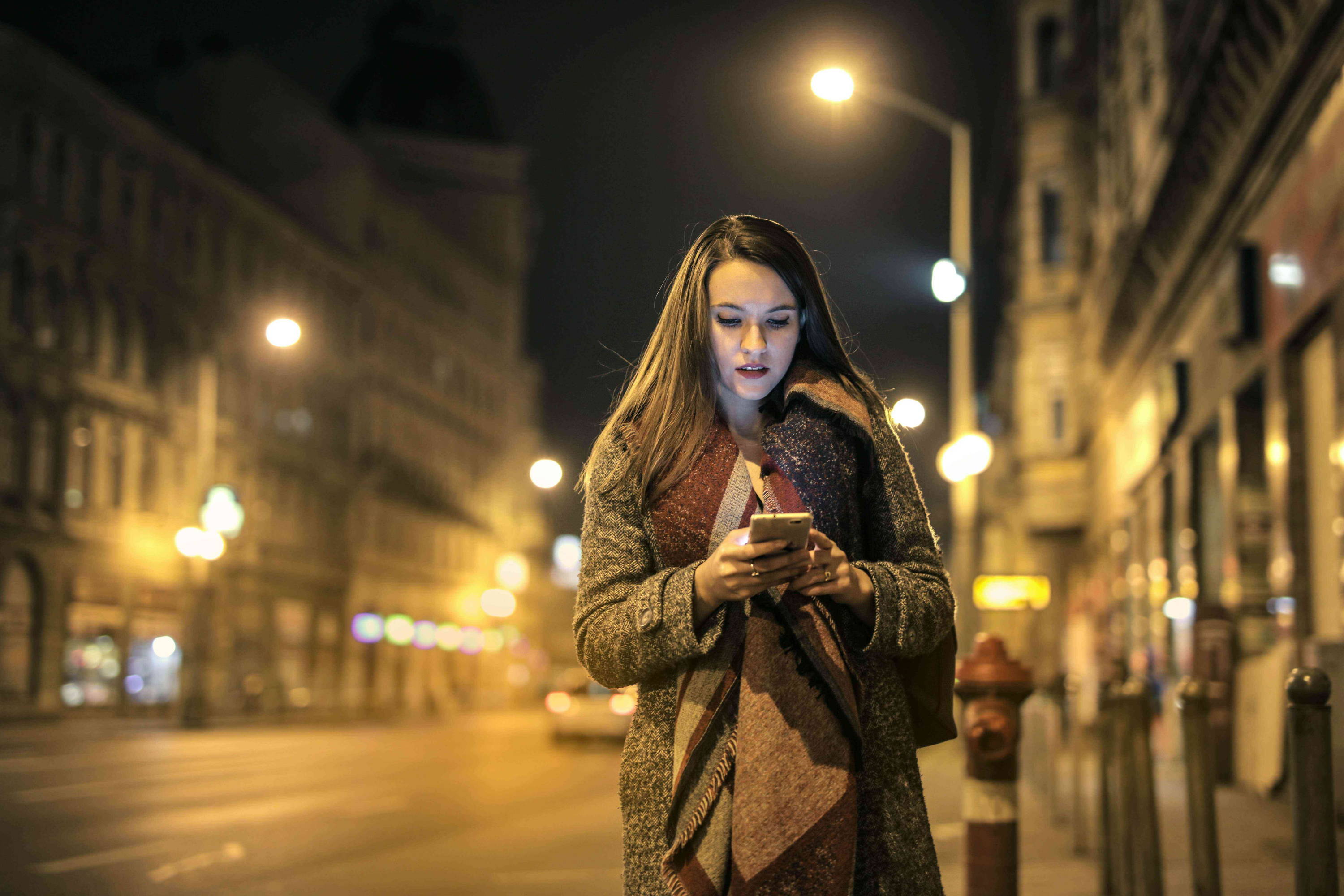 Woman using her phone walking alone at night in a busy city, staying safe as woman in the UK