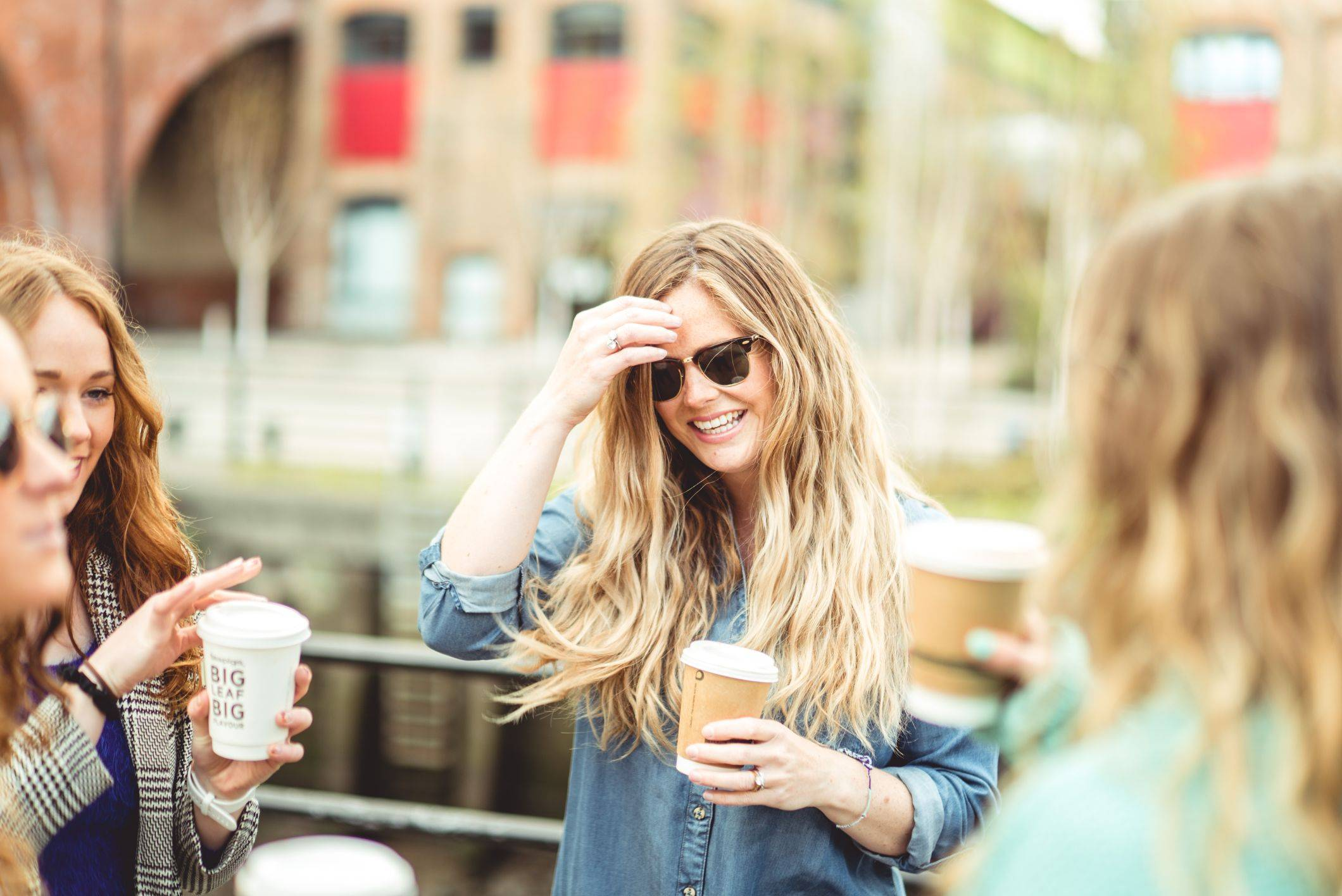 Image of two girls drinking coffee in the sun