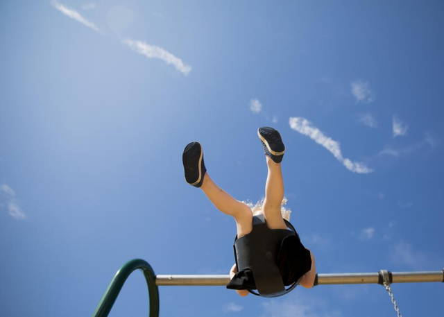 a child on a swing under a blue sky