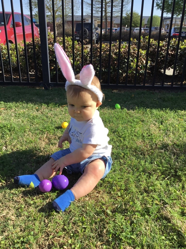 baby doing an Easter egg hunt wearing bunny ears at Primrose School of Clear Lake, daycare and child care center in 77062