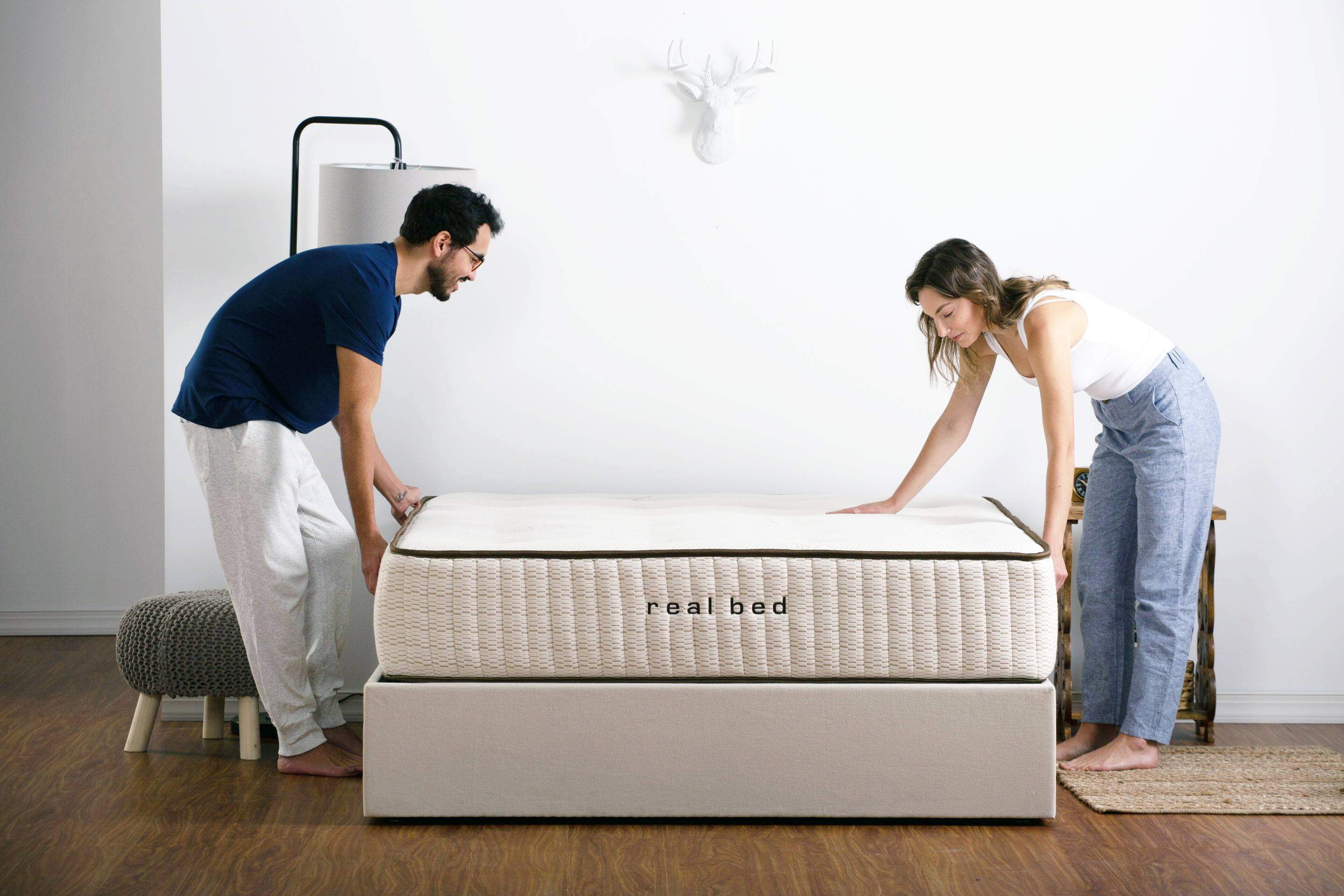Man and woman making a bed in stylish white bedroom. Image