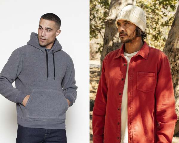 Man wearing sustainable fleece hoodie in dark grey alongside man wearing red flannel shirt with white ribbed beanie hat both from sustainable menswear brand outerknown