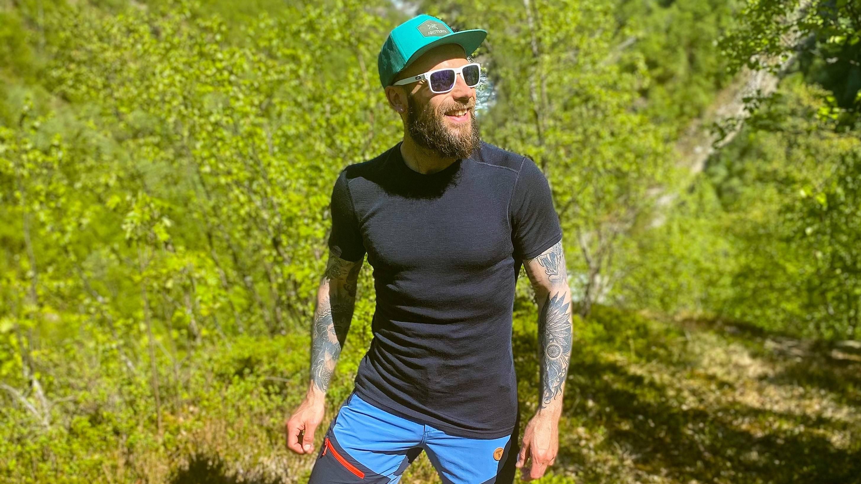 Frank Tindvik i mørk blå Tufte Merinoull T-skjorte, solbriller og caps. På tur i skogen.