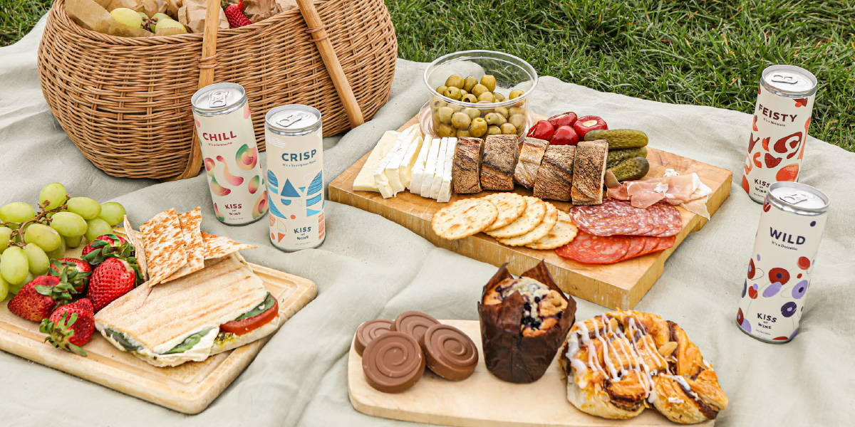 Picnic spread of toppings to go with baguettes and crackers paired with our light Kiss of Wine range on a summer's day.