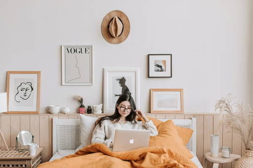 A woman in bed with her legs covered by a blanket, doing her work - Photo by Vlada Karpovich from Pexels