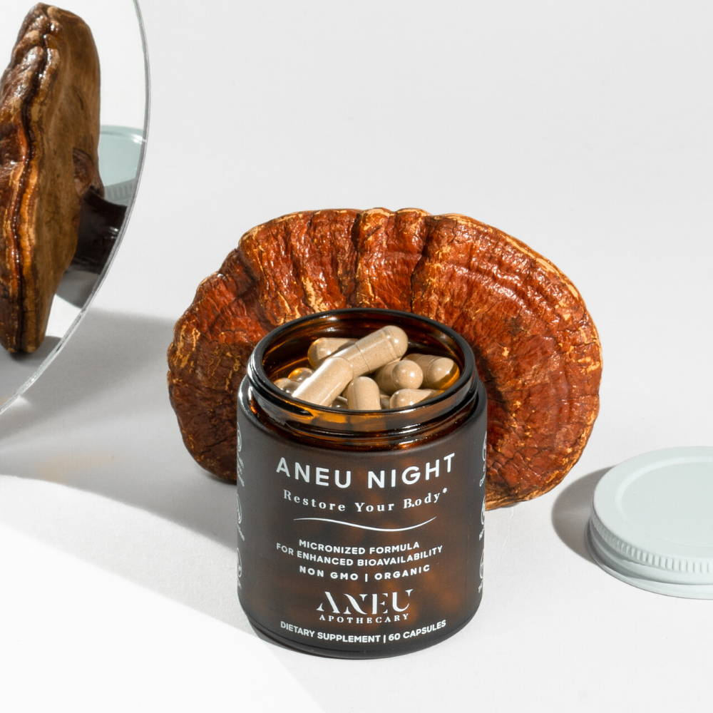 open bottle of aneu night in front of a reishi mushroom