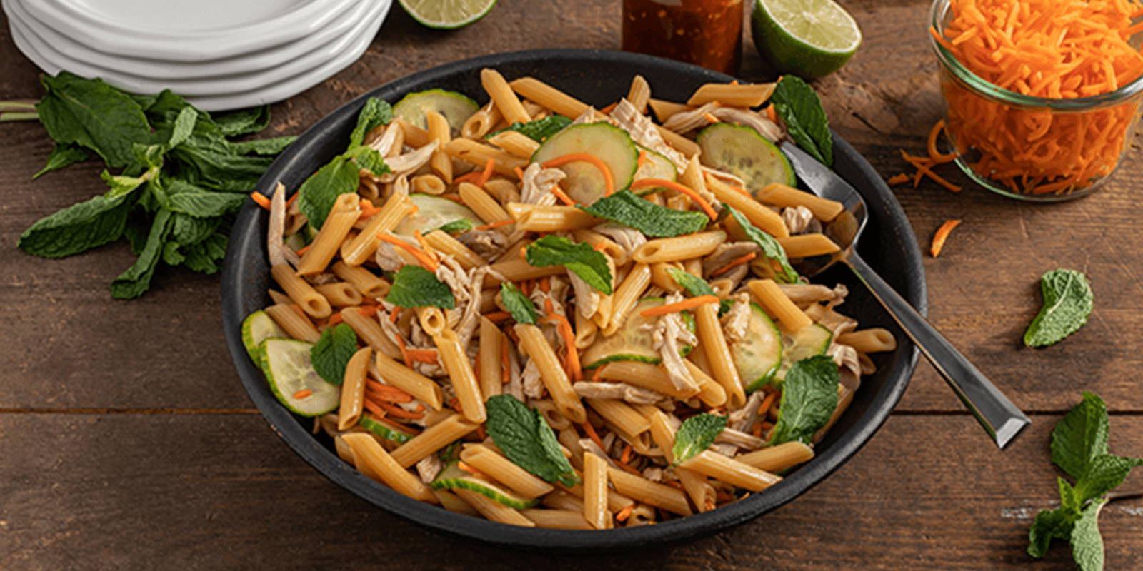 Bowl of pasta salad with cucumber, chicken, carrot, and mint.