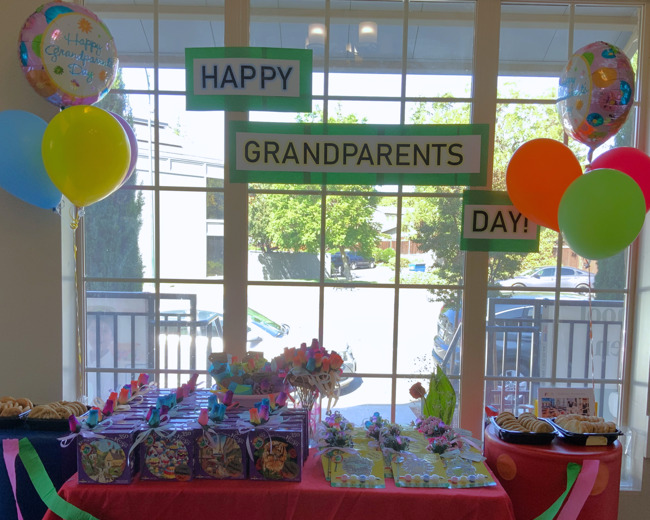 happy grandparents day sign, balloons, cookies, and gifts for our primrose community grandparents