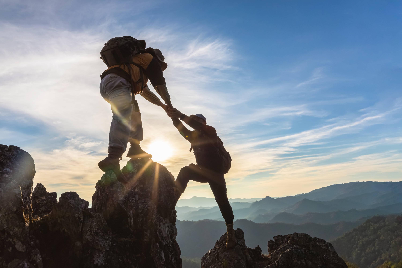 Ein Wanderer hilf einem Mann den Gipfel zu erklimmen.