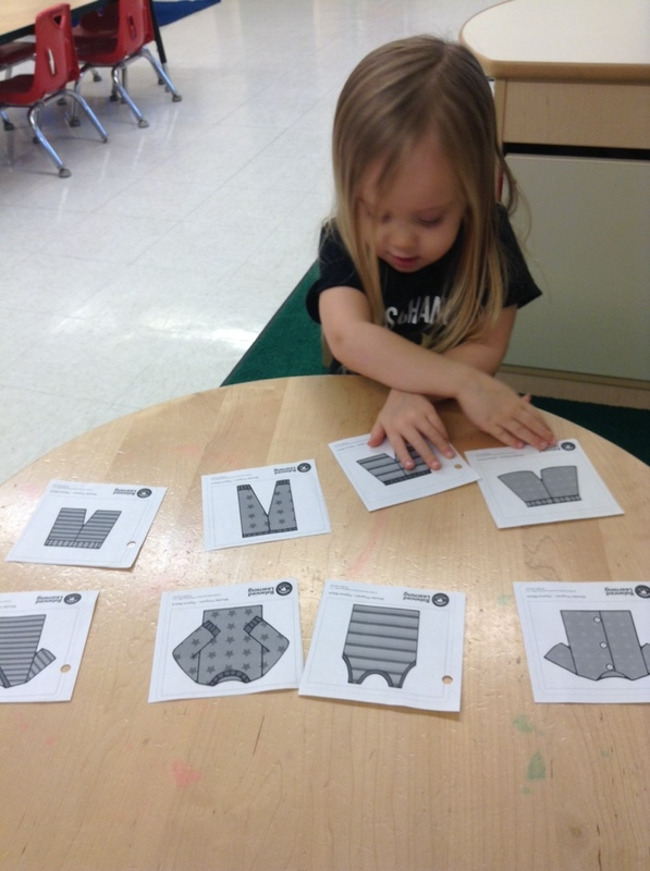 Two year old girl practices matching in the Preschool Pathways classroom at Primrose School of Clear Lake in Clear Lake, TX.